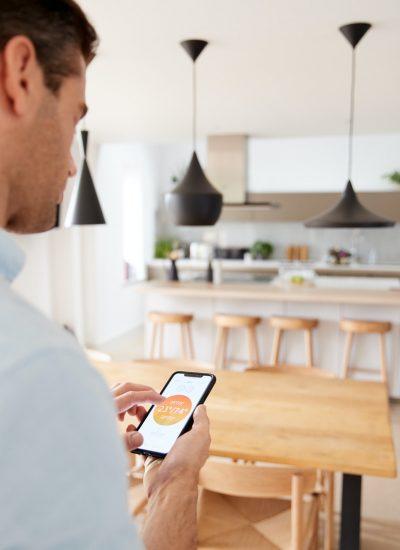 Mann som bruker smarthus-app for å styre varme